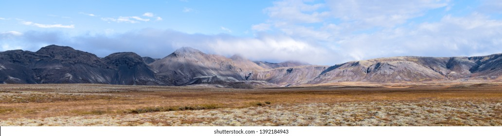 Landscape panoramic panorama view of Laugarvatn mountains with clouds covering on golden circle in Iceland during day and blue color sky in autumn