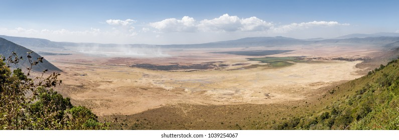 Landscape panoramic view Ngorongoro caldera, vulcano cliff wall, dry salt lake and rivers in bottom of crater, white clouds, October 2017 - Ngorongoro national reserve,Tanzania,Africa