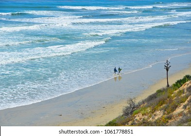 Landscape with panoramic view of two surfers walking with their surfboards, on the shoreline of Carlsbad State Beach in San Diego, Southern California.