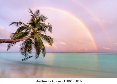 Landscape of paradise tropical island beach, sunrise sunset with beautiful rainbows over calm sea water. Wonderful scenery, tropical beach evening view. Palm tree with beach swing or hammock