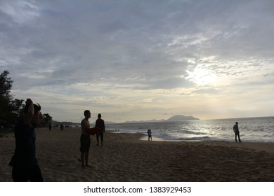 Landscape of paradise tropical island beach with various people under sunset - May 26, 2016, Singkawang City - Indonesia