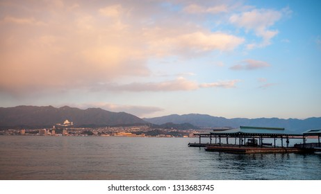 Landscape photo of the beautiful view that can be seen right outside the West Japan Railway Miyajima Ferry Terminal with the jetty in view, during the early morning, with dramatic clouds in the sky.
