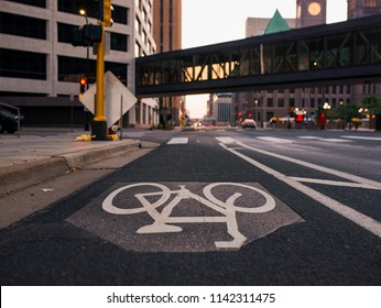 A landscape photo of the bike lane in down town Minneapolis. The photo is taken from the middle of the street with cityscape in the background.