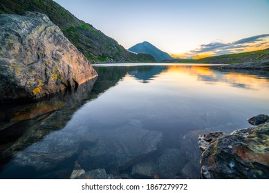 Landscape photo with Caltun alpine lake, rocky mountains, sharp ridges and stones in the morning light. Located in Fagaras Natural Park, Transylvania, Romania.