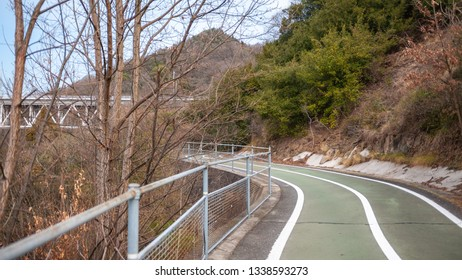 Landscape photo of the cycling lanes that lead to the first bridge on the Shimanami Kaido cycling route going from Onomichi which connects Mukoujima Island and Innoshima Island.