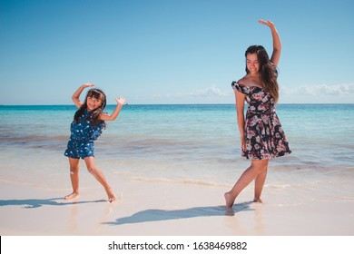 Landscape photo of mother and her daugther having fun at a Caribbean beach in Playa del Carmen, Mexico.