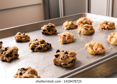 Landscape photo of multiple cookes / uncooked cookie dough with milk chocolate chips and smarties on the baking tray with soft light coming from behind.