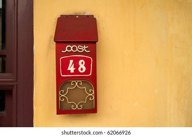 Landscape photo of retro letterbox against yellow wall