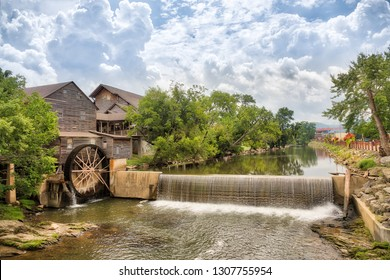 Landscape photo of a river and old mill with blue sky with clouds and the trees reflecting in the water.