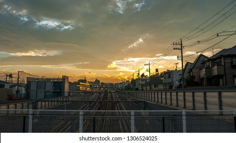 Landscape photo showing the beautiful sunset scene and multiple tracks on a railway in a typical suburban Japanese neighbourhood in the city of Tokyo in Japan.