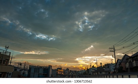 Landscape photo showing the beautiful sunset scene with dramatic clouds and multiple tracks on a railway in a typical suburban Japanese neighbourhood in the city of Tokyo in Japan.