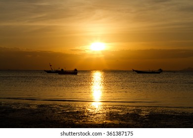 Landscape photo of sun setting into the ocean with fishing boats are floating