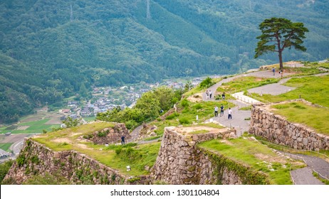 Landscape photo of tourists and local visitors walking around Takeda Castle Ruins located in Hyogo Prefecture's Asago City in Japan, which is a famous and popular side trip from nearby Himeji.
