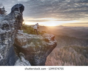 Landscape photograper with hand on camera and tripod. Woman climbed up on exposed rock for fall photos with his digital camera.