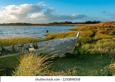 Landscape photograph of wetland foreshore with front end of abandoned wood boat in foreground.