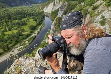 Landscape photographer takes pictures of nature in a rocky area, he climbed to the top of a mountain above a calm river.