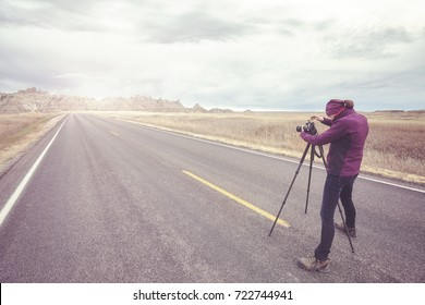 Landscape photographer takes pictures on an empty road at sunset, color toning applied, travel or work concept,  Badlands National Park, South Dakota, USA.