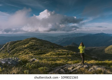 Landscape photographer taking a photo of the beautiful green valley at the sunset. At the scene, impressive mountains and white clouds at the blue sky.