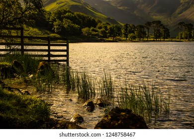 Landscape photography. Sunset over mountain lake, green hill, trees and silhouetted fence on lakeshore in rural Cumbria, North West UK.Tranquility of scenic british countryside.Pristine environment.