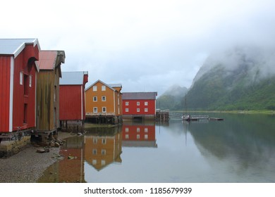 Landscape picture of colorful houses reflecting in the water at Sjøgata oceanfront in the town of Mosjøen, captured in Nordland county, Norway