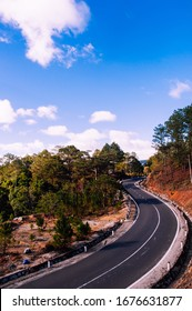 Landscape picture of a curving mountain road leading into the distant, pine trees and grass on the side of the road. Outdoors summer shot of Da Lat, Vietnam with blue sky and dreamy white clouds