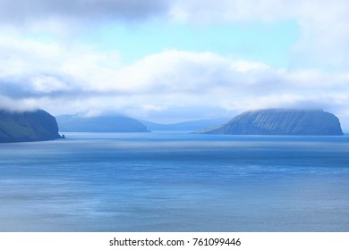 Landscape picture of a view of islands, blue water and blue skies, captured from the village of Kvikvik in Faroe Islands, Denmark