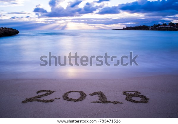 Landscape With Pinky Foggy Sea At Sunrise And The Sign 2018 Written On The Sand On Cloudy Sky Background