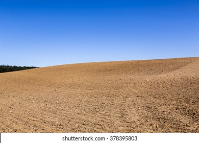 landscape with plowed field and blue sky