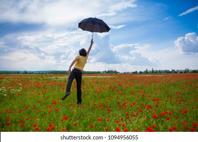 Landscape with poppies. Flies guy on umbrella
