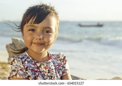 Landscape portrait of hispanic 4 year old girl sitting at the beach and looking at the camera with a calm expression . Taken at Playa del Carmen, Mexico.