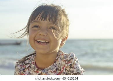 Landscape portrait of hispanic 4 year old girl looking up laughing with the sea on the background. Taken at Playa del Carmen, Mexico.