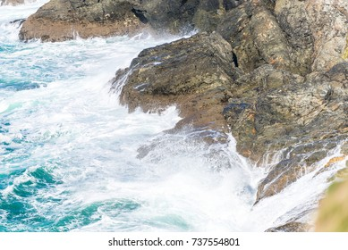 Landscape pounded by waves crashing onto the shore. Water crashes onto and runs off the granite that forms the coastline of North Cornwall.