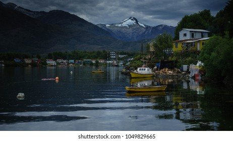 Landscape of Puerto Eden, small town located on the shore of the Pacific Ocean in Patagonia, Chile. You can see several boats stranded on the shore as well as houses of different colors and shapes.