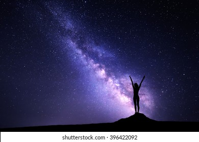 Landscape with purple Milky Way. Night sky with stars and silhouette of a standing sporty girl with raised-up arms on the stone