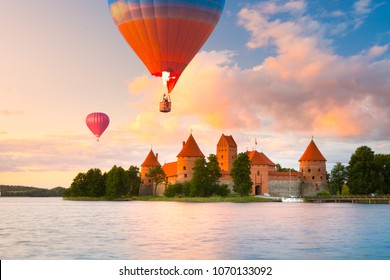 Landscape with red brick castle on island and flying air balloon in Trakai, Lithuania