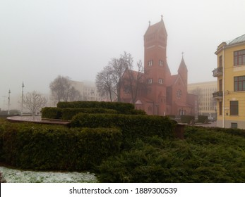 Landscape with a red catholic church in the city of minsk in winter during fog