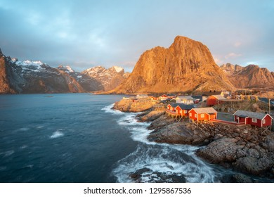 Landscape of red fishing rorbuer house village with sunrise light and mountain view in Lofoten island Hamnoy Norway