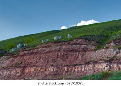 landscape, red mountains with dense vegetation against the background of the blue sky and small oblaky - Shutterstock ID 593910395