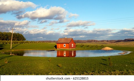 Landscape with red painted sauna cabin at round pond against blue cloudy sky background