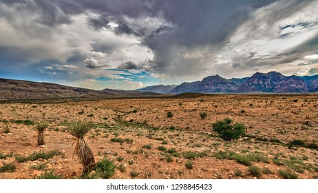 The landscape of Red Rock Canyon, Las Vegas, Nevada, with storm clouds brewing over the desert mountains, and blue sky peeking out.