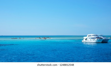 Landscape of the Red Sea. White yachts await tourists in the azure water of the Red sea, near a tiny white sandy island. Egypt, Sharm El Sheikh.