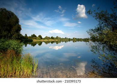 Landscape with reflections of the sky, clouds and trees  in the water of a lake