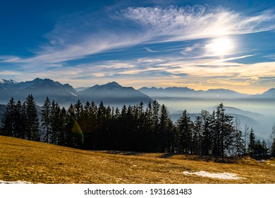 Landscape with the Rhine valley near Feldkirch shortly before and after sunset. Ground fog and veil clouds create a great atmosphere. Swiss mountains at the horizon, city and villages between hills