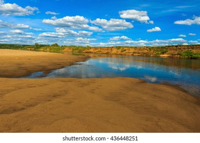 landscape of river and beach with cloudly sky, reflecting at water