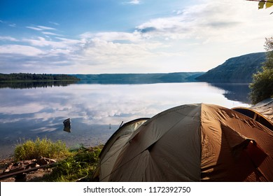 landscape of river with camping tent on first plan and river reflection of clouds over wide angle.Reflection.Cloydu sky.Travel