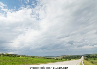 Landscape with a road and clouds. Beautiful views along the highway Chisinau Cimislia. The Republic of Moldova.