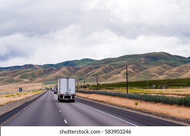 Landscape with a road running across the plain among the undulating corduroy hills and trucks moving by caravan on this straight road as eternal wanderers in the following ghost destination.