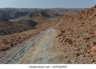 Landscape of rocky desert with winding track. View of (dry) Ugab river valley (down below), north of Brandberg, Damaraland, Namibia.