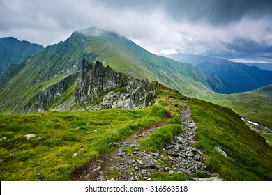 Landscape with rocky mountains and hiking trail in a cloudy day