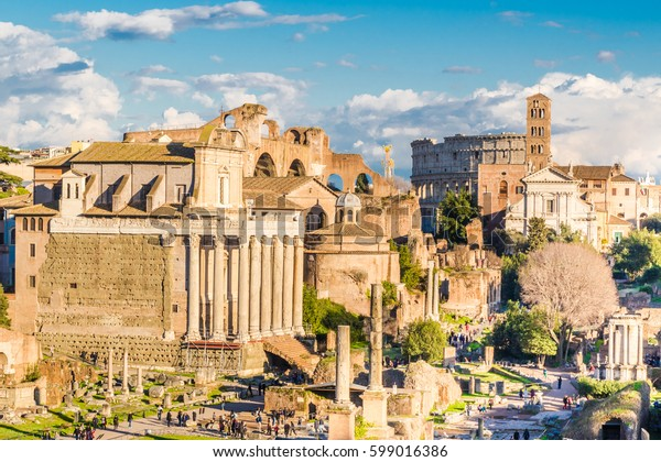 Landscape of Roman monuments in the rays of the setting sun. In the foreground the Temple of Antoninus and Faustina next the Temple of Romulus, the Santa Francesca Romana and the Colosseum